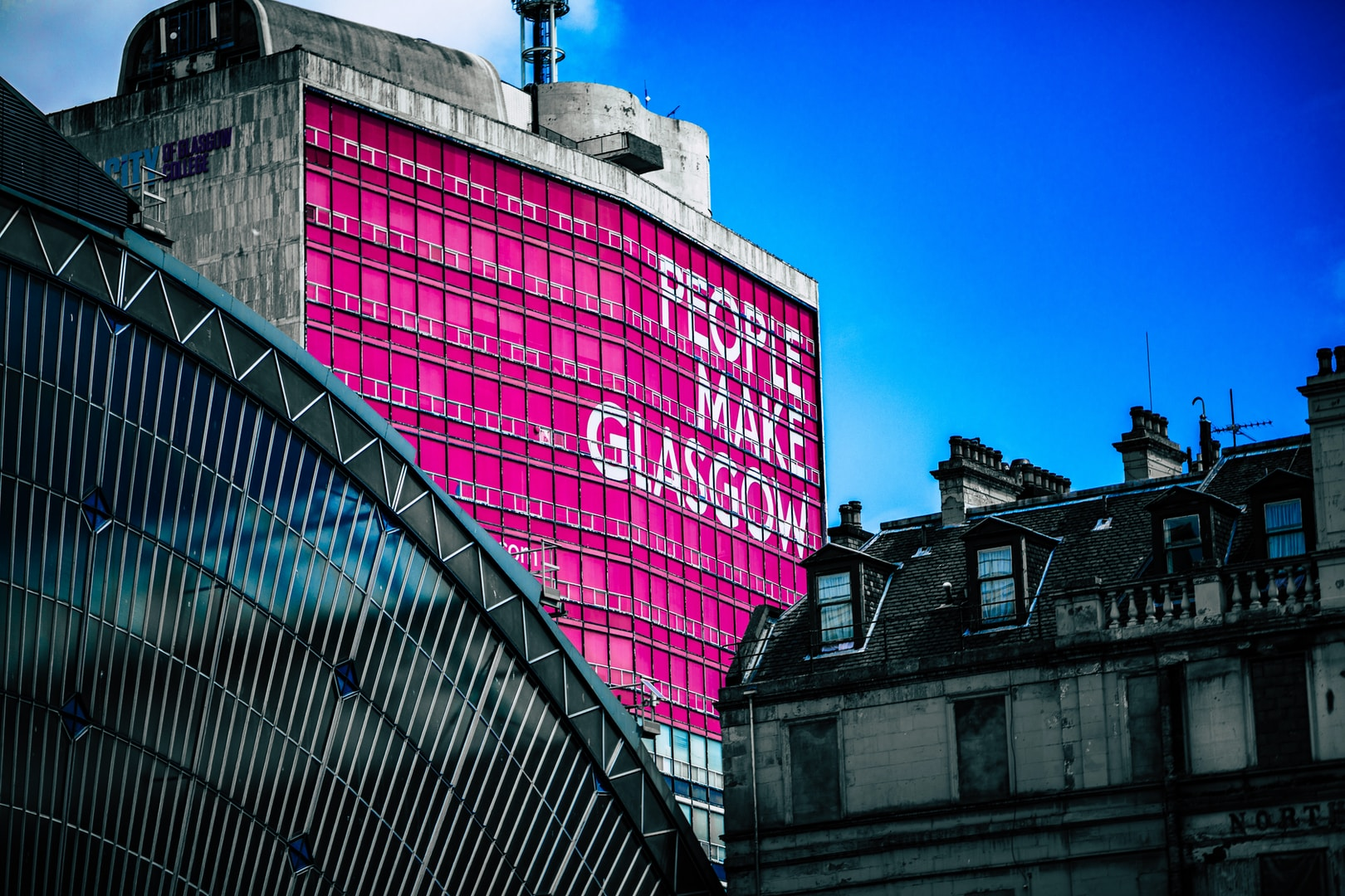 low angle view of building with People make Glasgow billboard