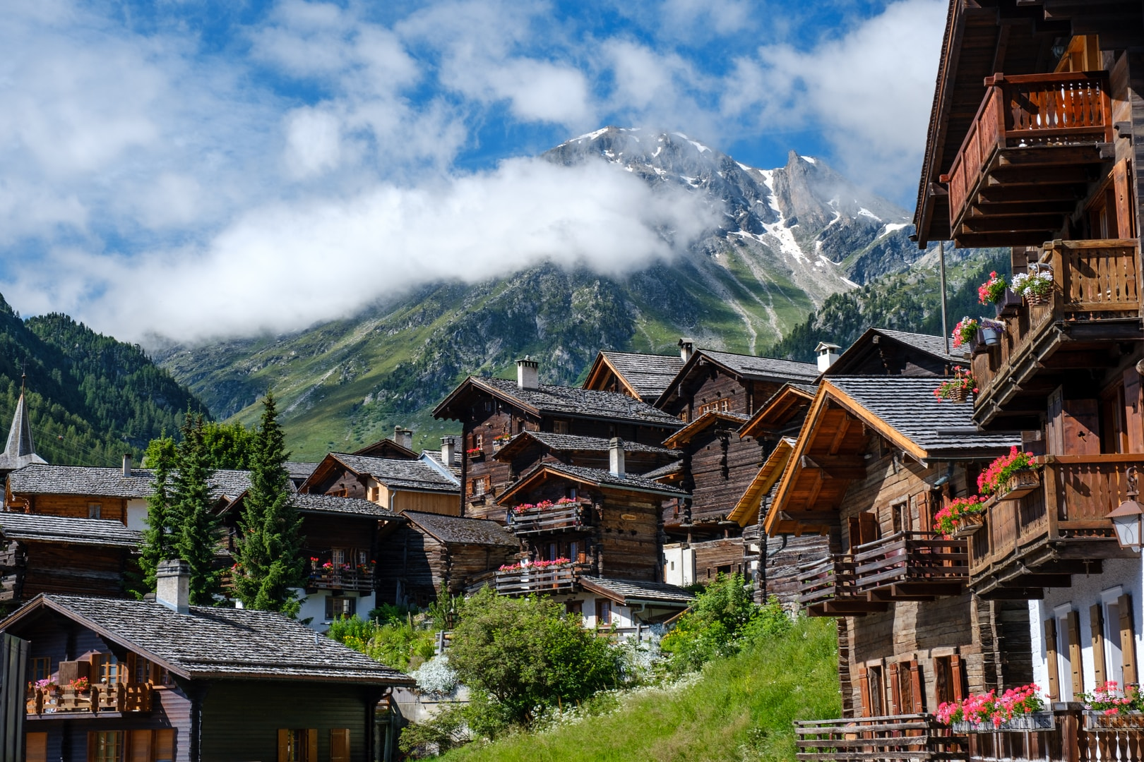 brown wooden houses near green trees and mountain under white clouds during daytime