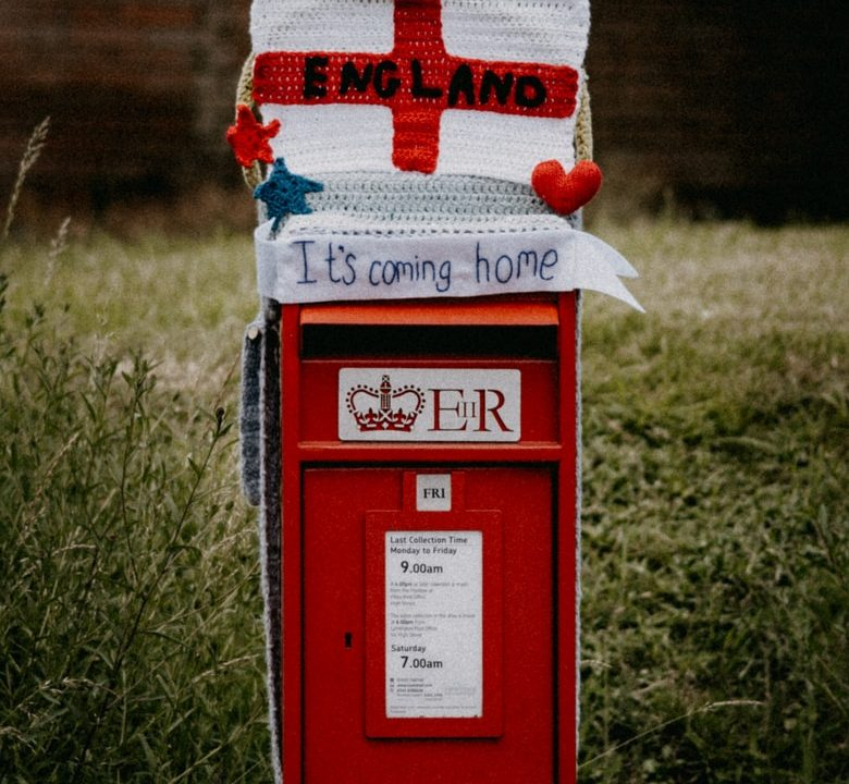 red and white mail box on green grass field